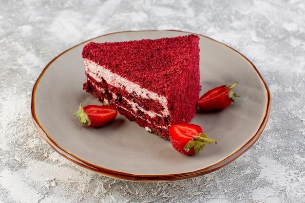 Widok z przodu z bliska kawałek czerwonego ciasta kawałek ciasta owocowego wewnątrz płyty z truskawkami na szarej powierzchni