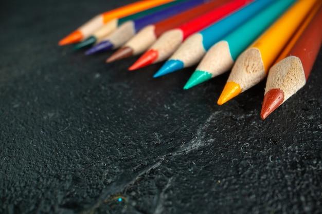 Widok z przodu z bliska kolorowe ołówki wyłożone ciemnym piórem do rysowania kolorowa szkoła fotograficzna