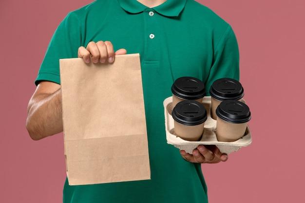 Widok z przodu z bliska kurier męski w zielonym mundurze, trzymający brązowe filiżanki kawy i pakiet żywności na różowym biurku