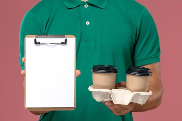 Widok z przodu z bliska kurier w zielonym mundurze, trzymający brązowe filiżanki kawy dostawy i notatnik na różowym biurku