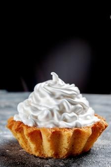 Widok z przodu z bliska mały kremowy tort pieczony pyszne na białym tle na szary, ciastko biszkoptowe słodki krem cukrowy