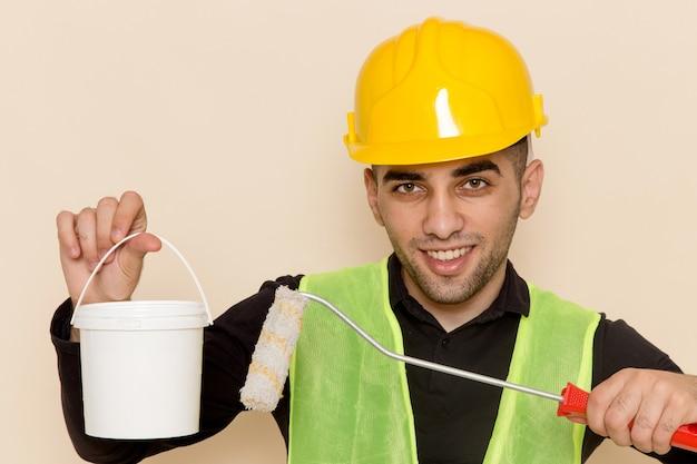 Widok z przodu z bliska mężczyzna budowniczy w żółtym kasku, trzymając pędzel i farbę na jasnym tle