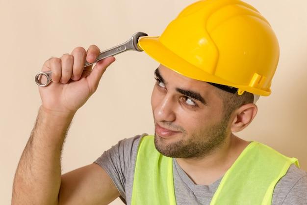 Widok z przodu z bliska mężczyzna konstruktora w żółtym kasku pozuje z narzędziem na jasnym tle