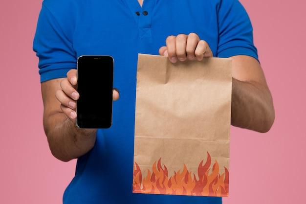 Widok z przodu z bliska mężczyzna kurier w niebieskim mundurze, trzymając pakiet żywności i telefon na różowej, jednolitej dostawie pracy usługi