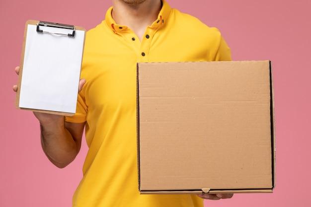 Widok z przodu z bliska mężczyzna kurier w żółtym mundurze, trzymając notatnik i pudełko dostawy żywności na różowym tle