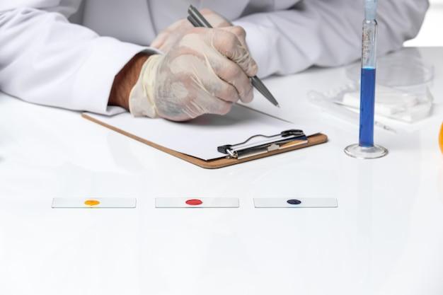 Widok z przodu z bliska mężczyzna lekarz w białym kombinezonie medycznym z maską z powodu covid pisania na białej przestrzeni