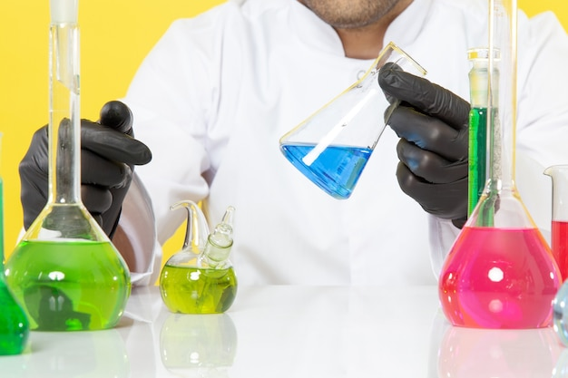 Widok z przodu z bliska młody chemik w białym garniturze przed stołem z kolorowymi roztworami pracujący z roztworami na żółtym biurku praca naukowa laboratorium chemia