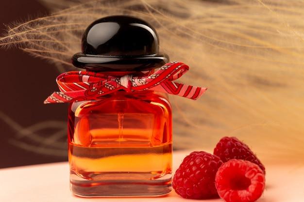 Widok z przodu z bliska pachnących malinami perfum wewnątrz kolby na fioletowej powierzchni