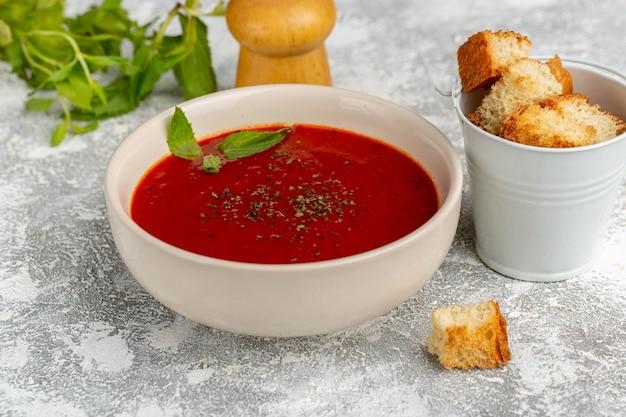Widok z przodu z bliska pyszna zupa pomidorowa z sucharami i zieleniną na szaro, zupa posiłek obiad warzywny