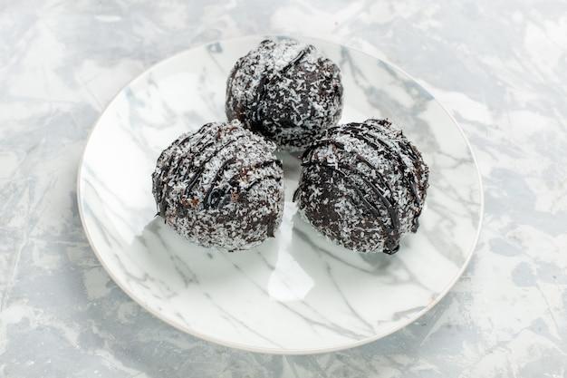 Widok z przodu z bliska pyszne czekoladowe kulki okrągłe ciasta z lukrem na jasnobiałym biurku piec ciasto czekoladowe ciasto cukrowe słodkie