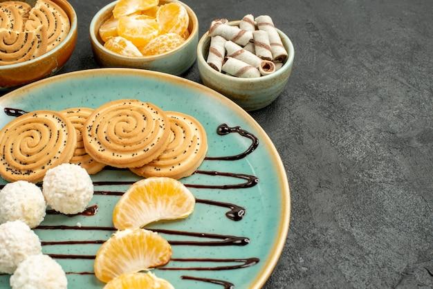 Widok z przodu z bliska słodkie ciastka z cukierkami kokosowymi na szarym biurku ciasteczka biszkoptowe słodkie