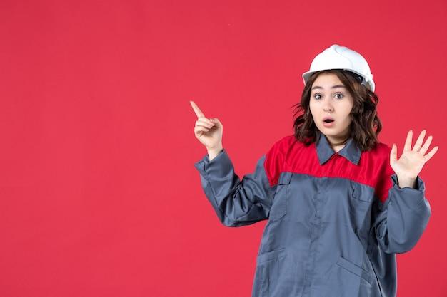 Widok z przodu z bliska zszokowana konstruktorka w mundurze z kaskiem i skierowana w górę na odizolowanej czerwonej ścianie