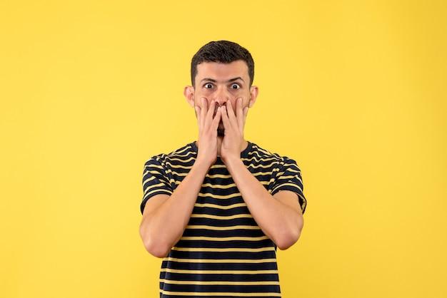 Widok z przodu z szeroko otwartymi oczami młody człowiek w czarno-białe paski t-shirt żółtym tle na białym tle