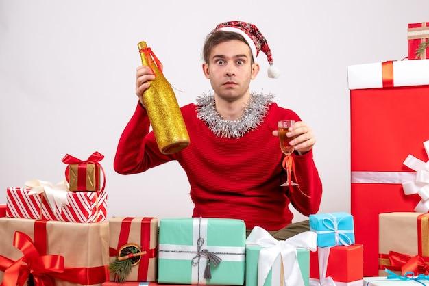 Widok z przodu z szeroko otwartymi oczami młody człowiek z santa hat trzyma szampana siedząc wokół świątecznych prezentów