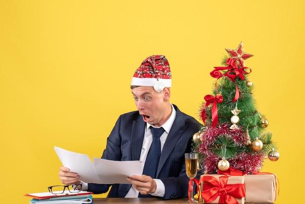 Widok z przodu z szeroko otwartymi oczami sprawdzania dokumentów siedzących przy stole w pobliżu drzewa xmas i przedstawia na żółto