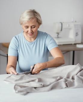 Widok z przodu z uśmiechniętą kobietą krawiecką w studio z tkaniny