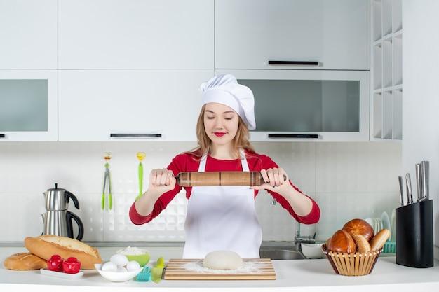 Widok z przodu zadowolona kucharka trzymająca wałek do ciasta w kuchni