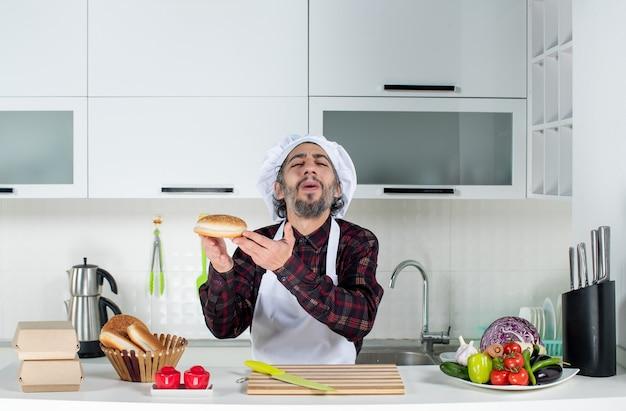 Widok z przodu zadowolonego męskiego szefa kuchni trzymającego chleb w nowoczesnej kuchni