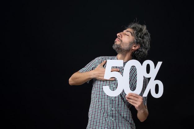 Widok z przodu zadowolonego mężczyzny z zamkniętymi oczami trzymającego znak na ciemnej ścianie