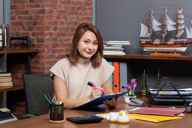 Widok z przodu zadowolonej kobiety używającej zakreślacza siedzącego przy ścianie