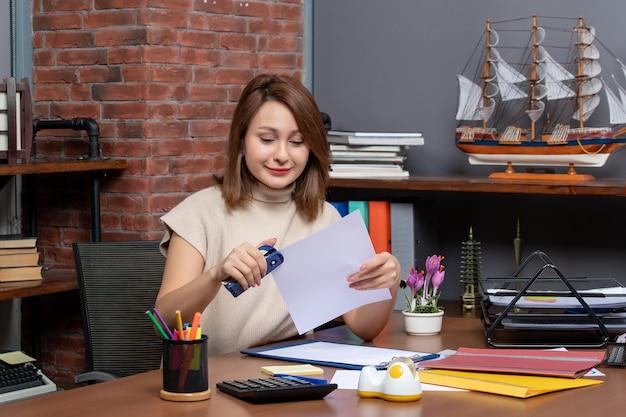 Widok z przodu zadowolonej kobiety używającej zszywacza siedzącego przy ścianie