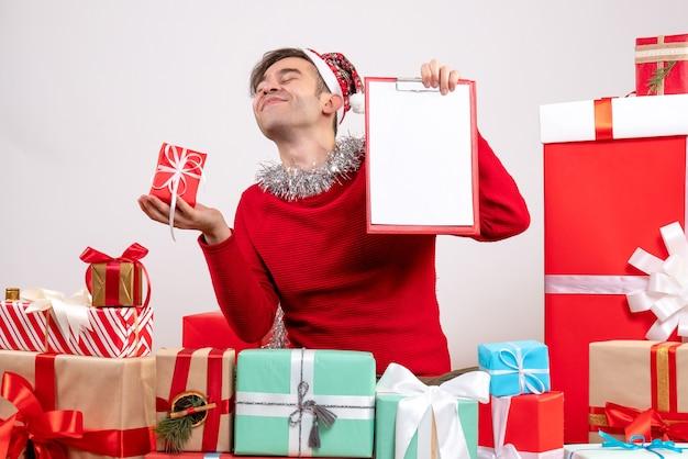 Widok z przodu zadowolony młody człowiek posiadający prezent i schowek siedzący wokół świątecznych prezentów