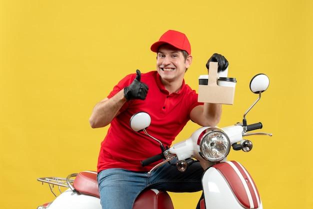 Widok z przodu zadowolony, pewny siebie kurier w czerwonej bluzce i rękawiczkach z kapeluszem w masce medycznej dostarczający zamówienie siedzący na skuterze, który trzyma zamówienia wykonując dobry gest