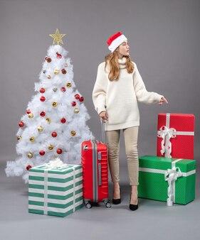 Widok z przodu zainteresowana dziewczyna z santa hat pokazując czerwone pudełko