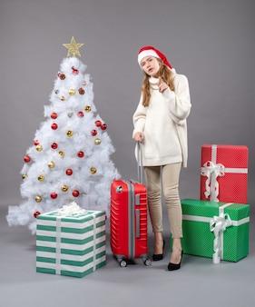 Widok z przodu zainteresowana dziewczyna z santa hat stojącej choinki i prezentami
