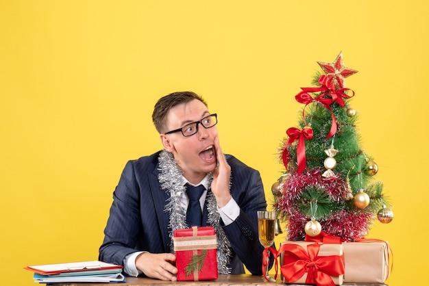 Widok z przodu zainteresowanego człowieka patrząc na prawo siedzącego przy stole w pobliżu choinki i przedstawia na żółto