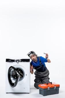 Widok z przodu zainteresowany mechanik trzymający stetoskop sprawdzający podkładkę na białej przestrzeni