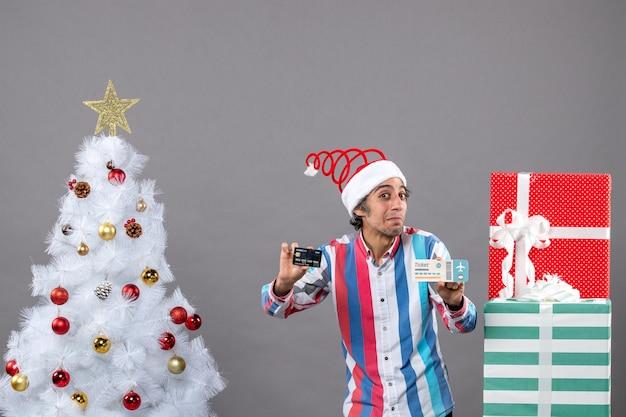 Widok z przodu zainteresowany mężczyzna posiadający kartę i bilet podróżny wokół choinki i prezentów