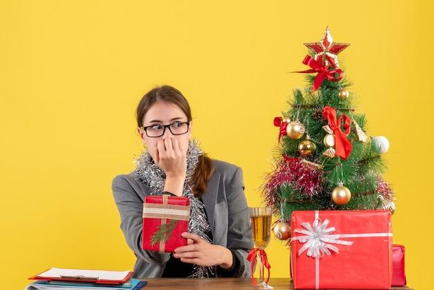 Widok z przodu zaintrygowana dziewczyna w okularach siedzi przy stole patrząc na prawe boże narodzenie drzewo i koktajl prezenty
