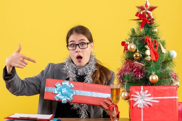 Widok z przodu zaintrygowana dziewczyna w okularach siedzi przy stole xmas drzewa i koktajl prezenty