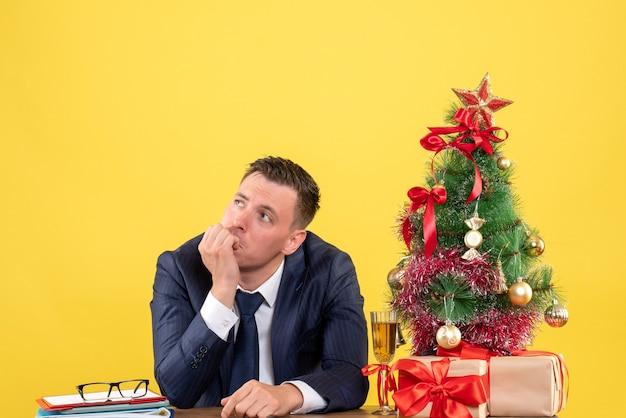 Widok z przodu zamyślonego człowieka myślącego o czymś siedzącym przy stole w pobliżu choinki i prezentów na żółto