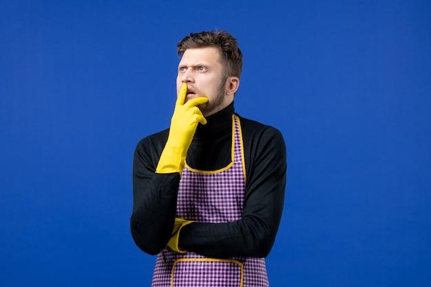 Widok z przodu zamyślonego młodego mężczyzny stojącego na niebieskiej ścianie