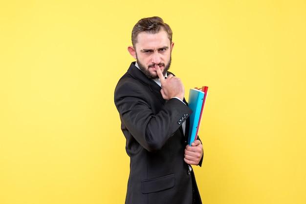 Widok z przodu zamyślony młody człowiek biznesmen dotyka ust palcem wskazującym i trzyma foldery na żółto