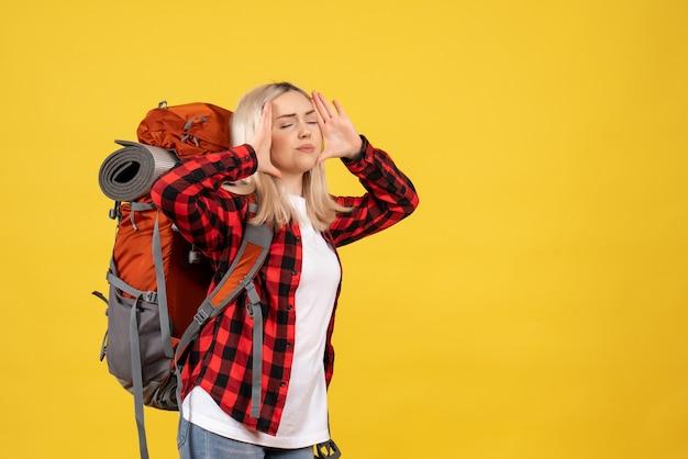 Widok z przodu zaniepokojona blondynka z plecakiem trzymającym głowę