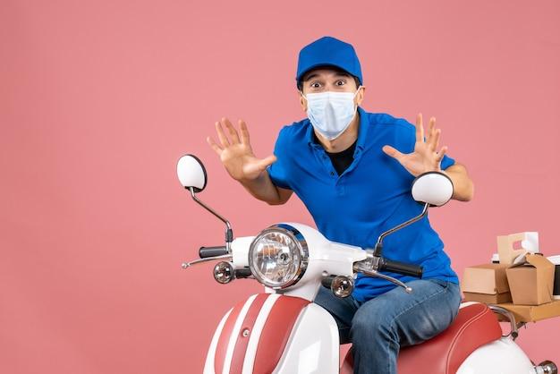 Widok z przodu zaniepokojonego faceta od dostawy w masce medycznej w kapeluszu siedzącym na skuterze na pastelowym brzoskwiniowym tle