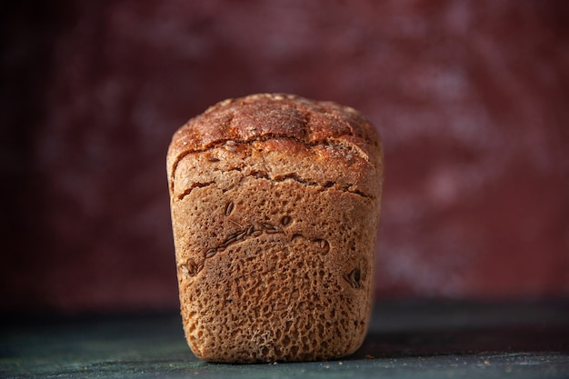 Widok z przodu zapakowanego czarnego chleba na bordowym niespokojnym tle z wolną przestrzenią