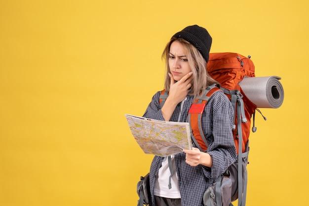 Widok z przodu zapracowanej podróżniczki z plecakiem, patrząc na mapę, myśląc o swojej podróży