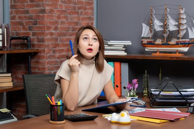 Widok z przodu zaskoczona biznesowa kobieta patrząca w górę siedząca przy ścianie