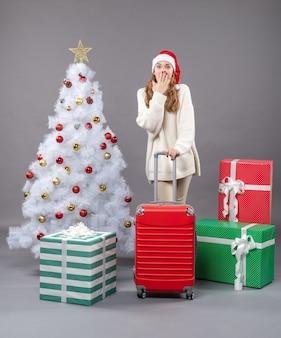 Widok z przodu zaskoczona dziewczyna xmas trzyma czerwoną walizkę stojącą w pobliżu drzewa xmas