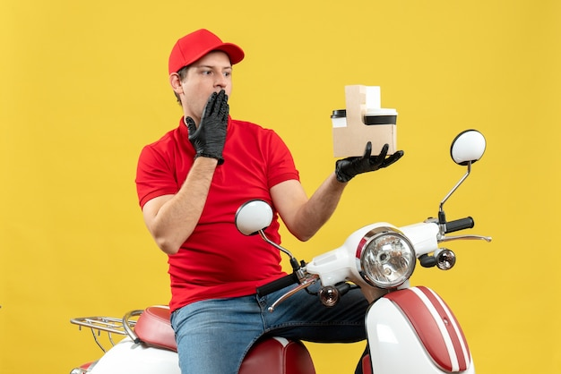 Widok z przodu zaskoczonego kuriera w czerwonej bluzce i rękawiczkach w masce medycznej dostarczającego zamówienie siedzącego na skuterze skupionym na zamówieniach