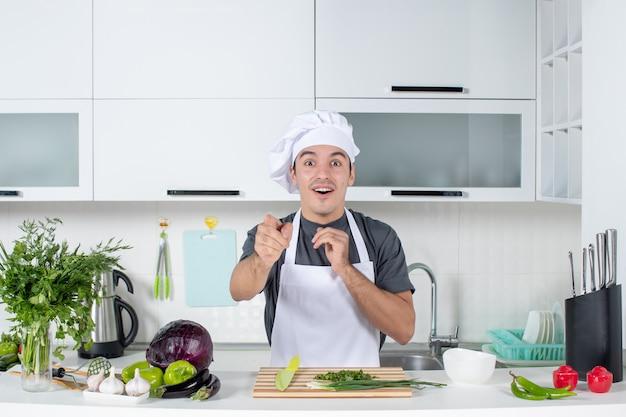 Widok z przodu zaskoczony męskim szefem kuchni w mundurze stojącym za stołem kuchennym