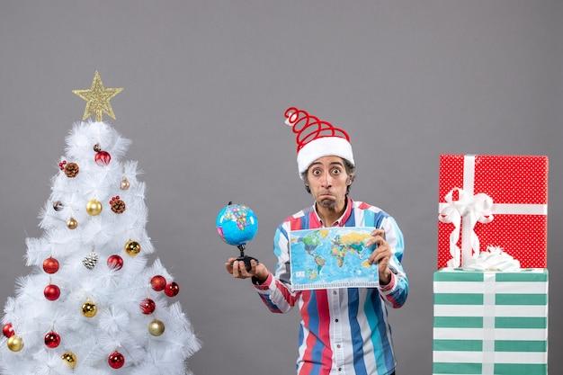 Widok z przodu zaskoczony mężczyzna ze spiralną wiosną santa hat trzyma mapę świata i kulę ziemską