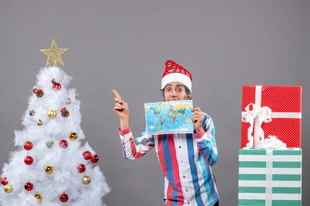 Widok z przodu zaskoczony mężczyzna ze spiralną wiosną santa hat trzyma mapę świata, wskazując na boże narodzenie drzewo