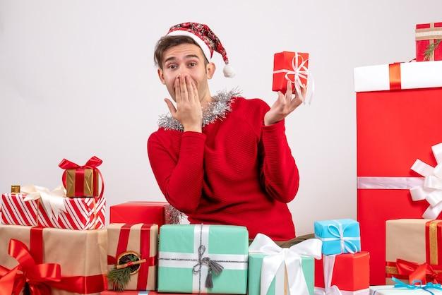 Widok z przodu zaskoczony młody człowiek siedzący wokół świątecznych prezentów