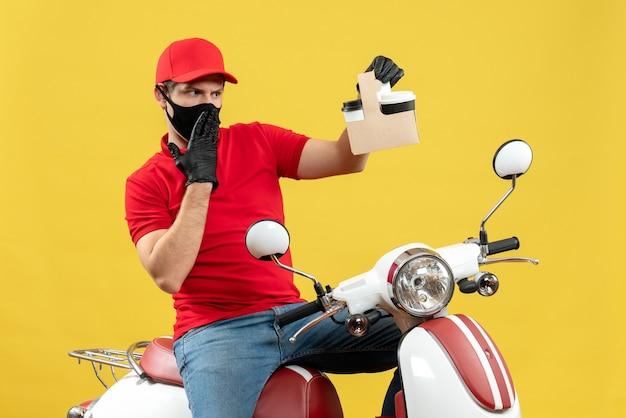 Widok z przodu zaskoczony skoncentrowany zajęty kurier w czerwonej bluzce i rękawiczkach w masce medycznej siedzi na skuterze