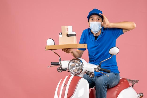 Widok z przodu zastanawiającej się męskiej dostawy w masce w kapeluszu siedzącej na skuterze dostarczającej zamówienia na pastelowym brzoskwiniowym tle